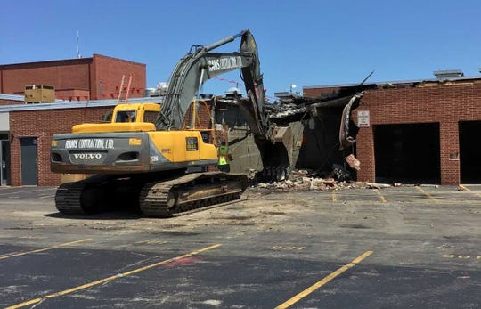 An excavator works to demolish a garage on the west side of Cedarburg High School's technology education wing.
