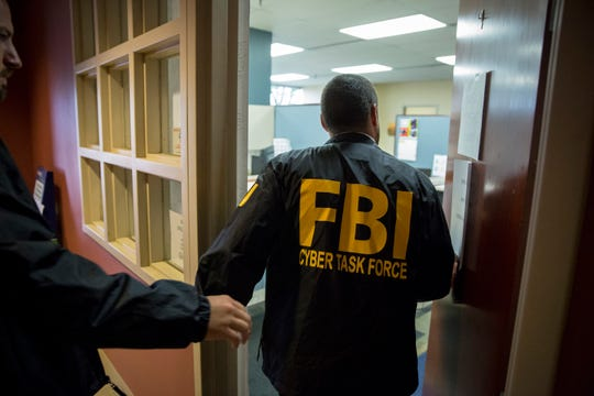 FBI agents and support staff enter and exit two city hall office that house the Muncie Sanitary District administration office and sewage utility during a raid Tuesday afternoon as they collected documents and computers. This is the latest in a series of raids related to corruption at city hall.