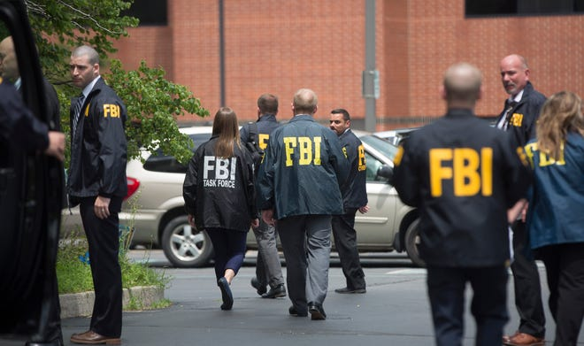 Nine agents leave city hall for their vehicles on July 16 after raiding two Muncie Sanitary District offices inside the building. The FBI also arrested the MSD administrator  and a local businessman.