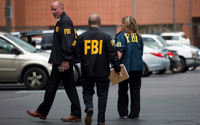 Nine agents leave city hall for their vehicles after raiding two Muncie Sanitary District offices inside the building on July 16, 2019. The FBI also arrested the district administrator of MSD and a local businessman.