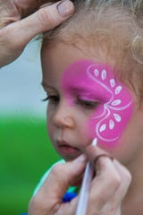 Young event attendee Stella, 4, granddaughter of David McQuiddy, gets her face painted at the fish fry last year.