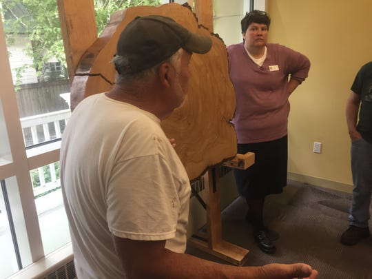 Master carpenter, John Cooper (left), discusses his work on the tree slice, as Library Director Anita Carroll listens.