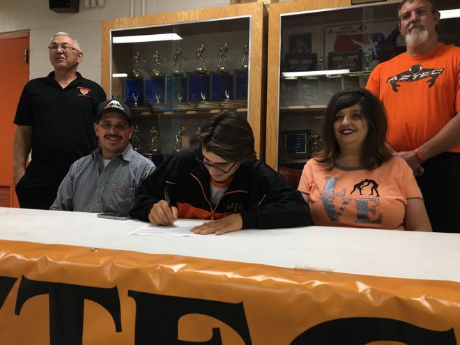 Aztec's Cody Candelaria signs his national letter of intent on Tuesday to continue his wrestling career at Otero Junior College.