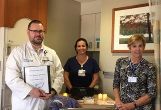 The Venerable Kevin Hickey, Beaumont Royal Oak Chaplain, nurse manager Kristen  Chaulk, and No One Dies Alone volunteer Sue Bay are accompanied by the special cart which volunteers use as they provide compassionate care for patients is the final hours of their life through the No One Dies Alone program. The cart contains hand crocheted afghans, reading materials, and other soothing items for end of life comfort.