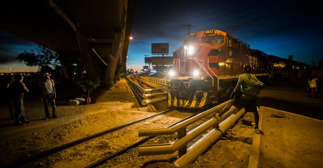 Central American migrants watch as a train prepares to leave a depot in Mexicali, Mexico.