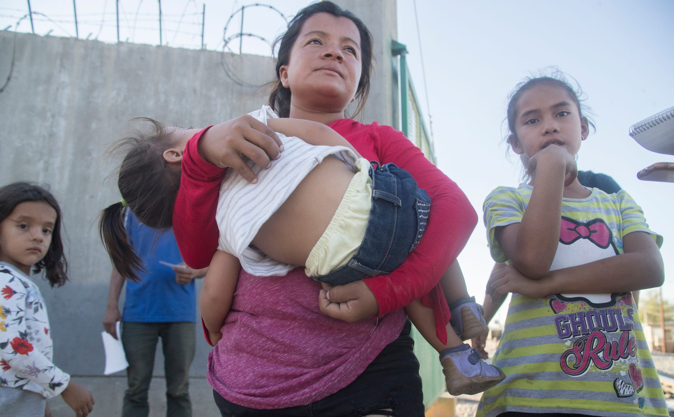 Evelin Ponce holds her 2-year old daughter, Evelin, while her other daughters, Fernanda, 9, right, and Anais, 6, flank her as they wait for a train they can jump aboard to take them south out of Mexicali, Mexico.