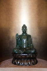 A jade statue of the Buddha seated on a bronze lotus throne by artist Lyle Sopel at the Palm Springs home of the late philanthropist Jim Houston. It is not available for purchase at an estate sale that opens July 19.