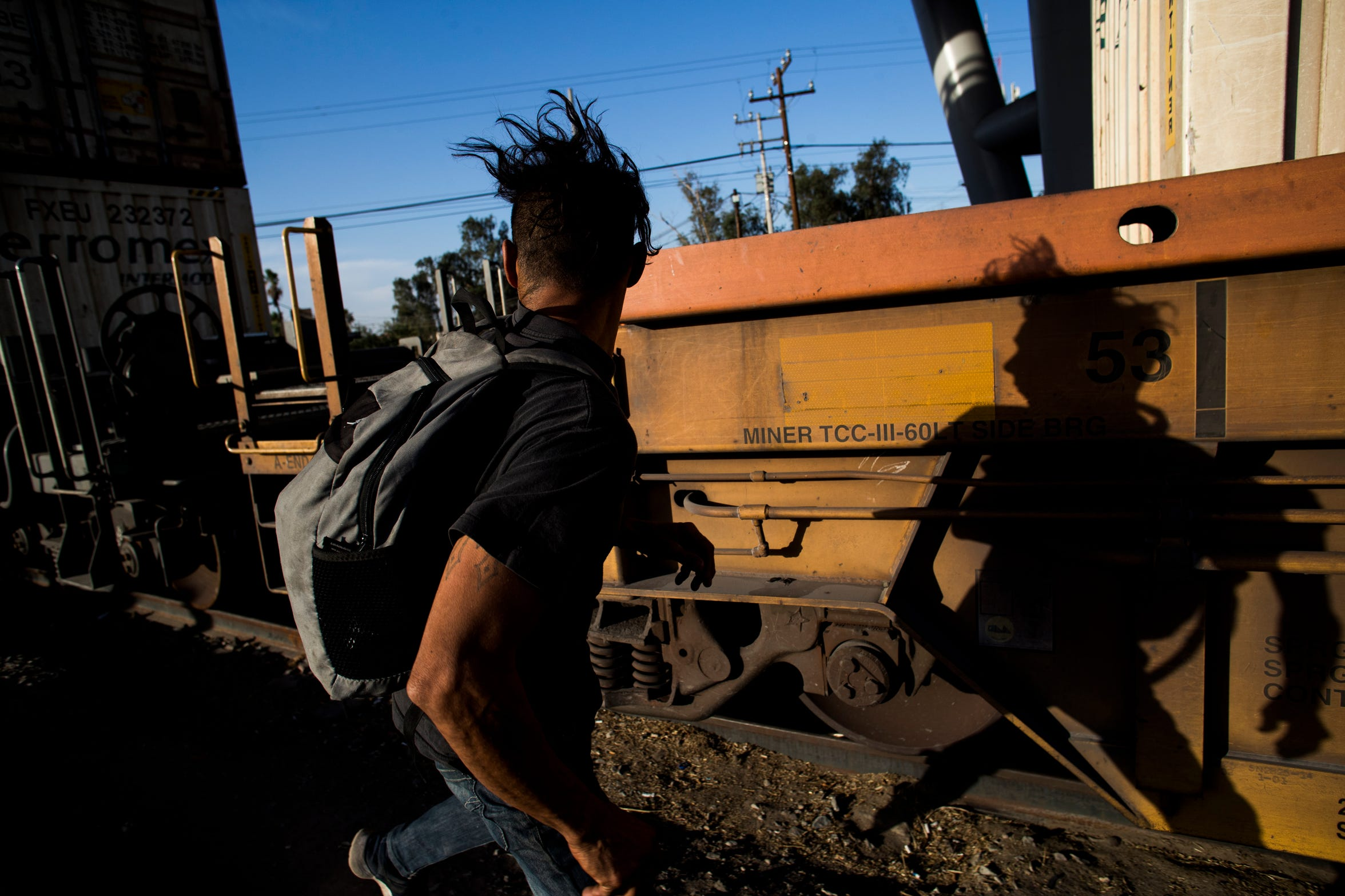 A Central American migrant runs beside a moving train he hopes to jump aboard in order to ride it south.