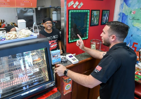 Omar Ramos, right, places an order with owner Joe Perez at Joe's Caribe Caribbean Cuisine restaurant on North Ninth Avenue in Pensacola on Tuesday.