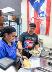 Owner Joe Perez, right, and manager Yashira Rivera box an order of Jamaican vegetable patties at Joe's Caribe Caribbean Cuisine restaurant in July.