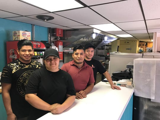 From left to right, Hermerson Hunildo, cashier; Jacqueline Tucios, Salvadorean food chef; Ermeglido Hunildo, owner; and Dimas Vail, Mexican food chef, work together to create the international Hispanic food at Blessing Restaurant, 1 E. Walnut St.