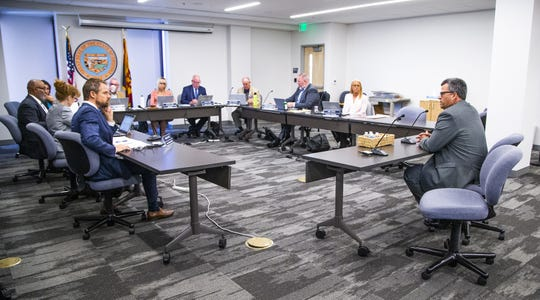 Franklin Lambert, right, addresses the Arizona Board of Funeral Directors and Embalmers in Phoenix, Tuesday, July 16, 2019.  The board is considering revoking the license for the funeral home he owns.