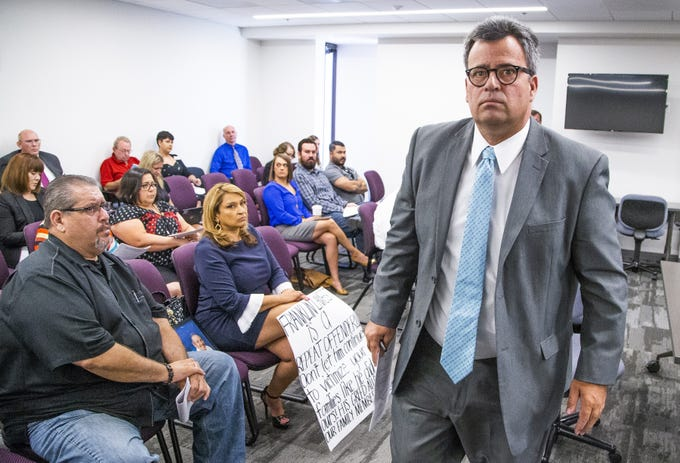 Stella Munoz, whose mother Rachel died in 2011, left, holds a sign at the meeting of the Arizona Board of Funeral Directors and Embalmers in Phoenix, Tuesday, July 16, 2019. Munoz accuses Franklin Lambert, right, of mistreating her mother's body.
