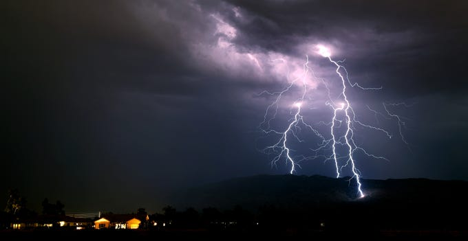 Lighting strikes straddle a ridge in the Rincon Mountains east of Tucson, looking east from the Agua Caliente Wash at Houghton Road on Sunday, July 14, 2019, Tucson, Ariz.
