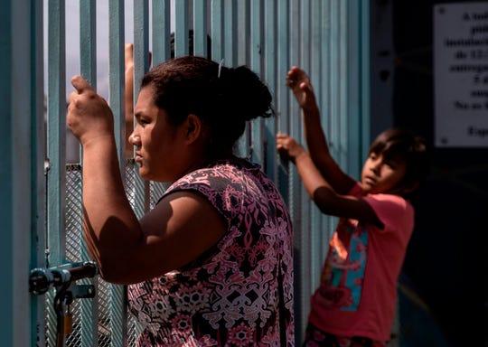 Migrantes centroamericanos observan a través de la cerca fronteriza desde México.