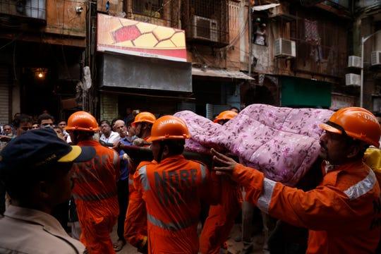 Rescatistas cargan el cuerpo de una víctima, tras derrumbarse el edificio.