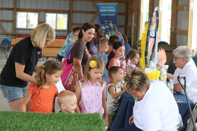 """Gayle Millinge of Croghan Colonial Bank grabs some prizes for a few children as part of a """"Money Day"""" game at the Ottawa County Fair on Tuesday."""