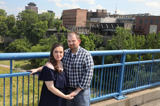 Sharon DeWitt and fiancee Jeffrey Knight stand together on the Pont de Rennes bridge over the High Falls gorge in the High Falls District in downtown Rochester Wednesday, July 10, 2019.  Behind the couple is La Luna Restaurant and their popular outdoor patio that overlooks the gorge.