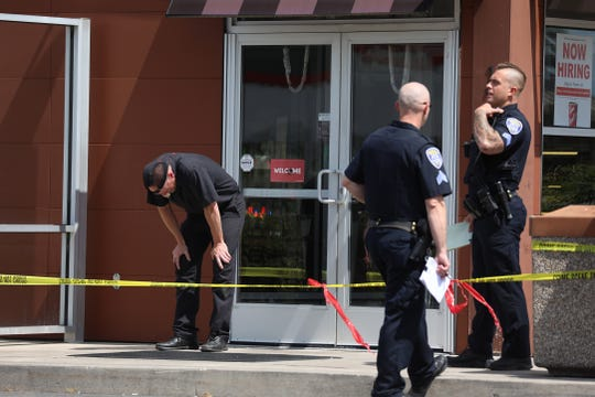 A Tim Hortons employee reacts after the discovery of Bryce Raynor's body in a grease trap outside the restaurant.