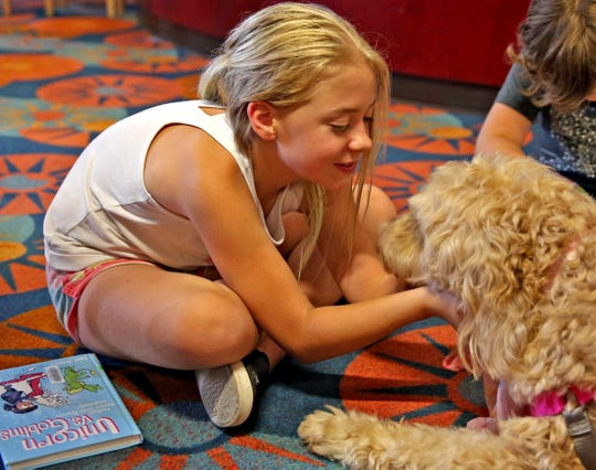 Eleanor Perkins plays with Hattie as part of the Tail Waggin Tutors program at Stephens Central Library on Tuesday, July 16, 2019.