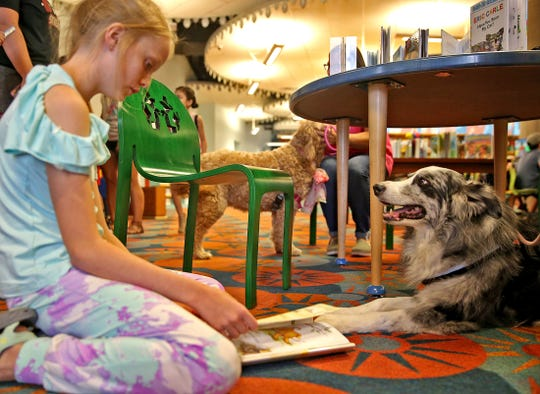 Elizabeth Anderson reads to Chloe the dog as part of a program to help kids feel more at ease learning to read at Stephens Central Library on Tuesday, July 16, 2019.