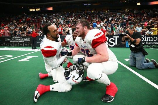 Storm quarterback Lorenzo Brown (L) celebrates the team's United Bowl win with teammate Forrestal Hickman Saturday night in Glendale, Ariz.
