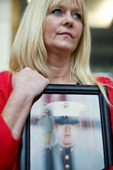 Kathy Davis holds a portrait of her son Kindall Johnson for a portrait at Strong Hall in the Missouri State University campus in Springfield, Mo. on May 17, 2016. Johnson, a Marine and MSU student, committed suicide. Davis is helping organize the Ride to Live event Saturday.