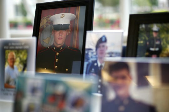 A framed portrait of Kindall Johnson, a Marine and MSU student who committed suicide, sits among photographs of other young military veterans who recently ended their lives as well.