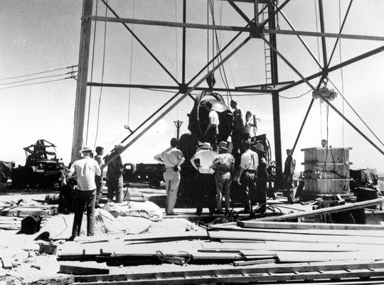 FILE - In this July 6, 1945, file photo, scientists and workmen rig the world's first atomic bomb to raise it up onto a 100 foot tower at the Trinity bomb test site near Alamagordo, N.M. A compensation program for those exposed to radiation from years of nuclear weapons testing and uranium mining would be expanded under legislation that seeks to address fallout across the western United States, Guam and the Northern Mariana Islands.(AP Photo/File )