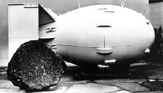 """FILE - This Oct. 15, 1965, file photo shows a """"Fat Man"""" nuclear bomb of the type tested at Trinity Site, N.M, and dropped on Nagasaki, Japan in 1945, on view for the public at the Los Alamos Scientific Laboratory Museum. A compensation program for those exposed to radiation from years of nuclear weapons testing and uranium mining would be expanded under legislation that seeks to address fallout across the western United States, Guam and the Northern Mariana Islands. (AP Photo, File)"""