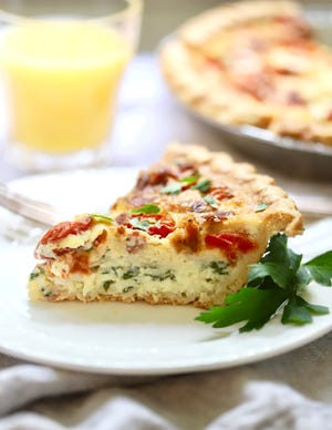A slice of spinach, bacon, and tomato quiche satisfies for breakfast, lunch or dinner.
