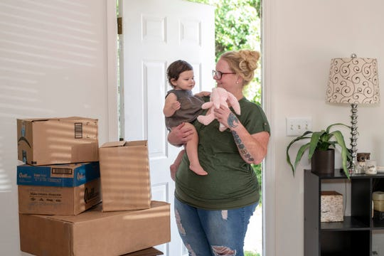 Madison and her mother, Jessica Bright, at the doorway of their new home after their move from Mary's Shelter.