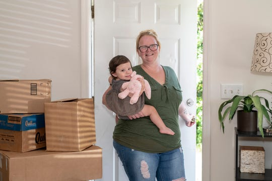 Jessica Bright, holding her daughter Madison, stands at the doorway of their new home.