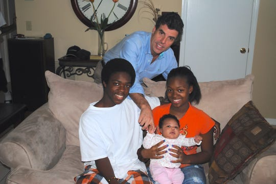 Dr. Glenn Tremml with one of Indian River Healthy Start Coalition's client families, from left, Deshawa, Jessica and baby Jakayla.