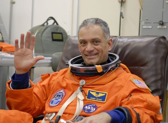 In this photo released by NASA, Space shuttle Atlantis mission specialist John Olivas  waves to the NASA cameraman while being suited up prior to making a trip to the pad at the Kennedy Space Center in Cape Canaveral, Fla. Friday, Feb. 23, 2007. The crew is at KSC rehearsing for their scheduled March 15, launch. (AP Photo/NASA)