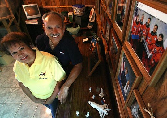 """10/10/2006 Juan and Carmen Olivas have a wall in their den with photographs of space shuttle astronauts, including their son, John """"Danny"""" Olivas."""