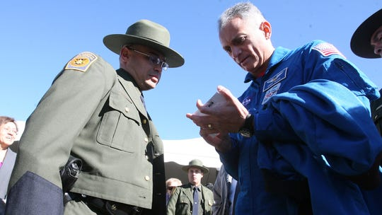 "01/26/2010 NASA astronaut John D. ""Danny"" Olivas signed an autograph for U.S. Border Patrol Agent Juan Carlos Escobar after a ceremony in which Olivas presented a Border Patrol flag that flew on the space shuttle Discovery in August 2009."