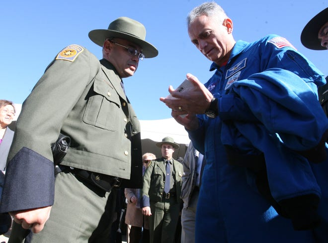 """01/26/2010 NASA astronaut John D. """"Danny"""" Olivas signed an autograph for U.S. Border Patrol Agent Juan Carlos Escobar after a ceremony in which Olivas presented a Border Patrol flag that flew on the space shuttle Discovery in August 2009."""