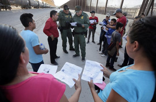 Border Patrol agents inspect documents from Central American asylum seekers on the border betwen El Paso and Juarez. Some of the documents appeared suspicious and family relationships were questioned.