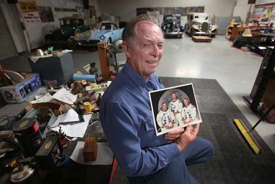 Rich Manley, a NASA engineer who worked on the Apollo project, including the moon landing is shown holding an autographed copy of the Apollo 11 crew in his workshop in Goshen, Calif., Tuesday, July 19, 2019.