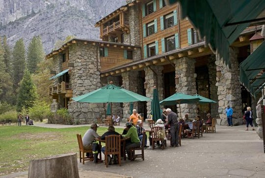 FILE - In this Oct. 24, 2015, file photo, people dine outside the former Ahwahnee hotel in Yosemite National Park, Calif. On Monday, July 15, 2019, Delaware North, a company that lost its contract to run Yosemite National Park's hotels, restaurants and outdoor activities, has settled a lawsuit with the National Park Service and the park's new concession operator over rights to the names of famous park landmarks. (AP Photo/Ben Margot, File)