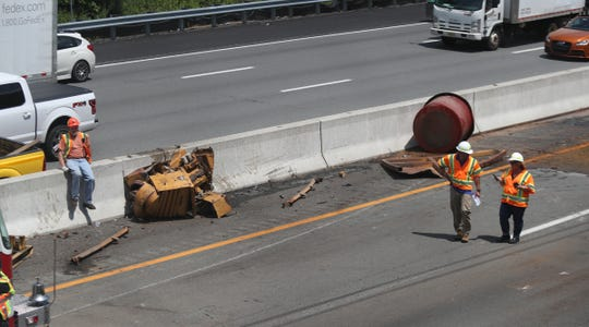 Debris litters the New York State Thruway at the Hungry Hollow overpass after the load of a tractor trailer struck the overpass in Chestnut Ridge on Tuesday, July 16, 2019.