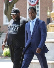 Andre Wallace, right, crosses the plaza in front of Mount Vernon City Hall on his way to the Mount Vernon courts, July 16, 2019.