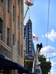 Workers install the sign for The Landmark on Lamar apartments Monday afternoon at the corner of Lamar and 11th Street.