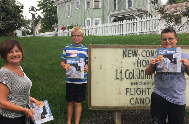 Debbie Allender, director of the John and AnnieGlenn Museum in New Concord, presents the book Apollo's First Moon Landing, to Landen Snell and Noah Green during Space Camp Tuesday.