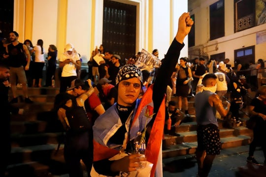 Demonstrators react after a series of clashes with police during a day of protests on Monday in San Juan, Puerto Rico.