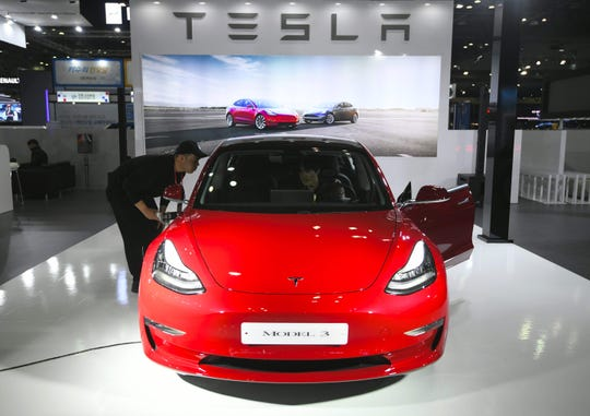 In this file photo taken on March 27, 2019 visitors look at a Tesla Model 3 during a press preview of the Seoul Motor Show in Goyang, northwest of Seoul.