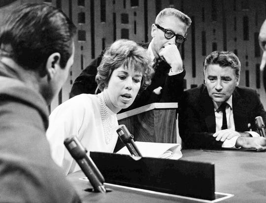 "Guest stars Carol Burnett and Peter Lawford, right, search for word clues and answers under the eye of host Allen Ludden (center) on CBS Television Network's ""Password"" in New York on Aug. 15, 1963."