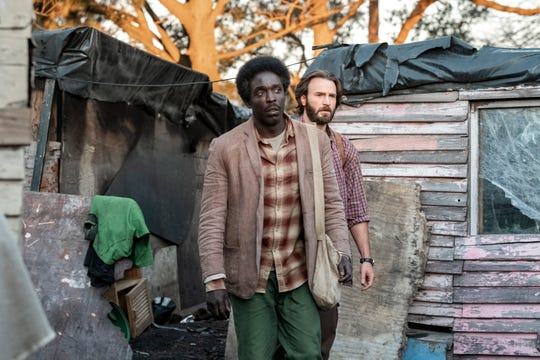 "Kabede Bimro (Michael Kenneth Williams, left) and Ari Kidron (Chris Evans) risk their lives to get Ethiopian refugees to Israel in the Netflix movie ""The Red Sea Diving Resort."""