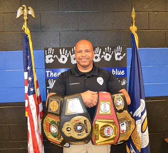 Alexandria police officer Anthony Deshautelle shows the belts he has earned boxing in Battle of the Badges events. He has donated two of the belts to the Alexandria Police Department in honor of fallen local police officers.